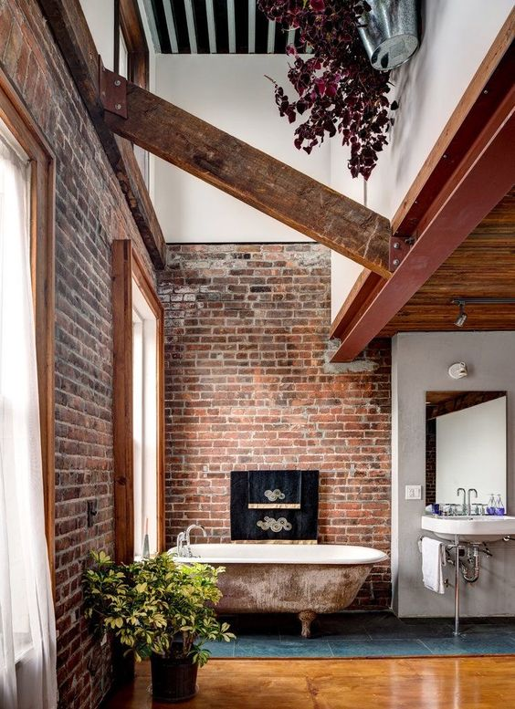 an industrial bathroom with brick walls, a shabby chic tub, wooden beams and a vintage sink
