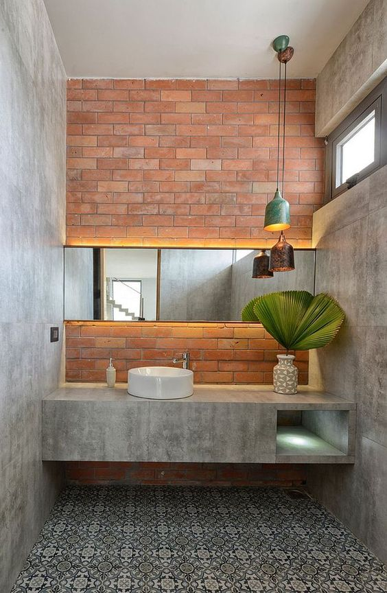an industrial bathroom with concrete walls and a built-in vanity, a patterned tile floor, a brick wall and catchy pendant lamps