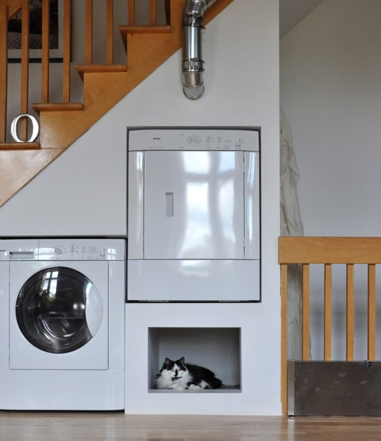 Utilizing residual space under stair to oranize a laundry space  is a great idea. You can also put a pet nook there.