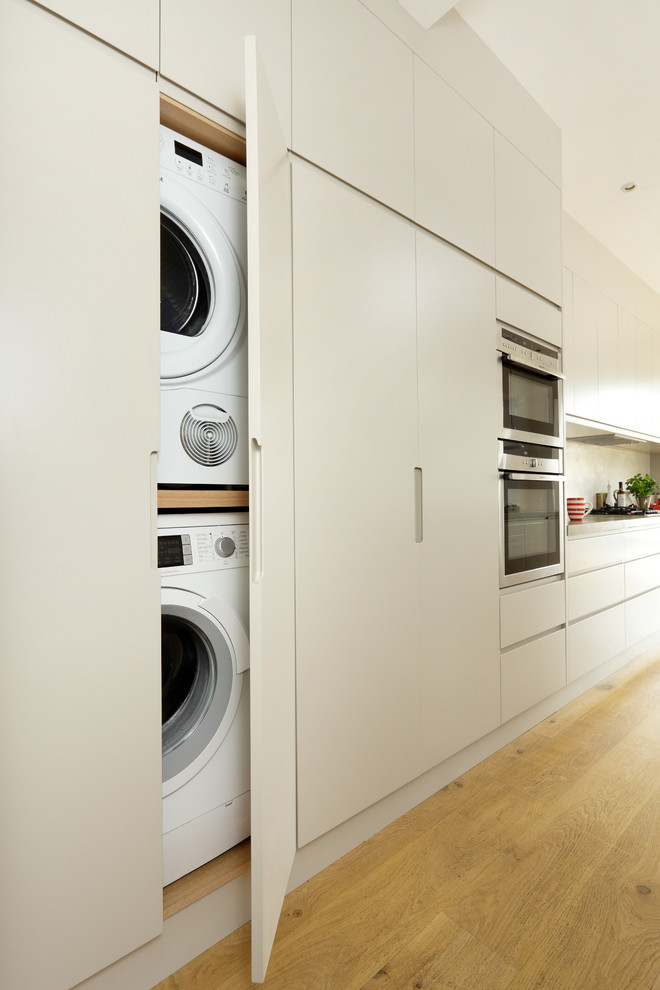 Custom cabinets allow to hide both a washing machine and a dryer without losing any space. (Cue & Co of London)