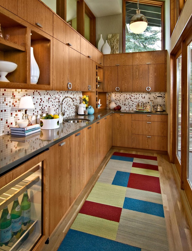 a rich colored wooden kitchen with a mosaic tile backsplash, a color block rug and much natural wood  (Design By Lisa)