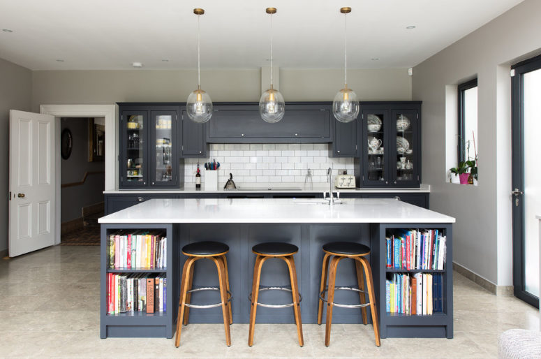 a grey mid-century modern kitchen with graphite cabinets, a large kitchen island with a white countertop and pendant lamps  (The Shaker Kitchen Company)