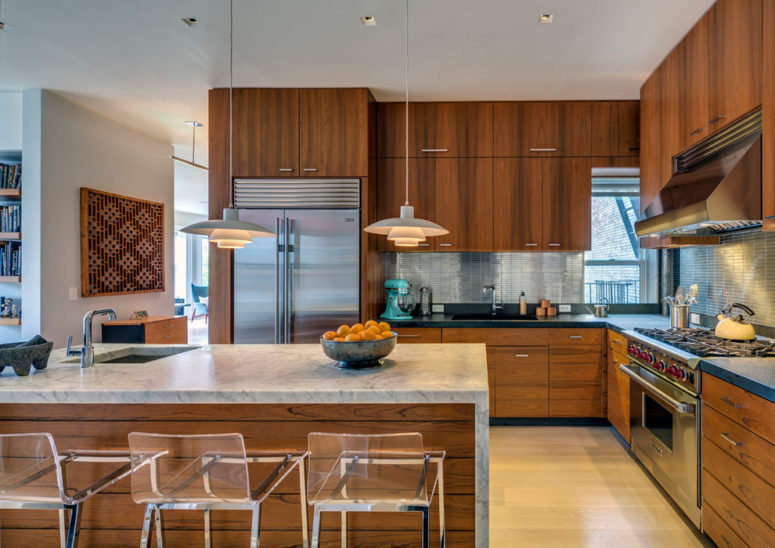a rich-stained mid-century modern kitchen with a large kitchen island with a stone countertop and pendant lamps  (Above Construction)