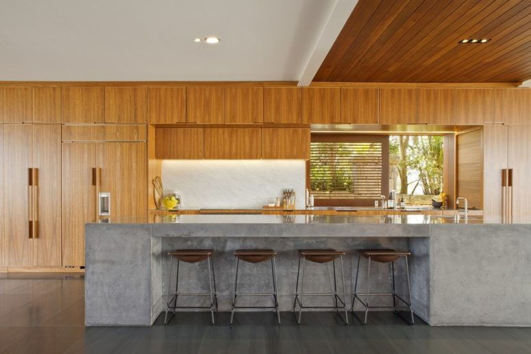 a rich-stained wooden kitchen with a concrete kitchen island and leather stools  (Richard Cole Architecture)