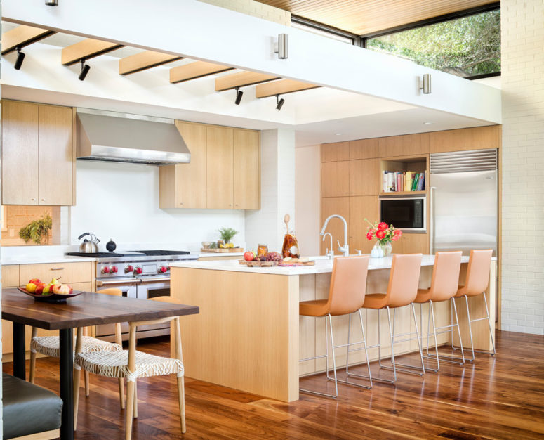 a lights-colored mid-century modern kitchen with white surfaces, orange stools and much light  (Allison Burke Interior Design)