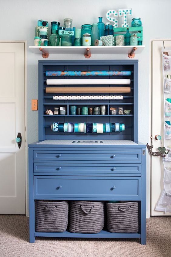 a blue storage piece with drawers and fabric basket and some open shelving