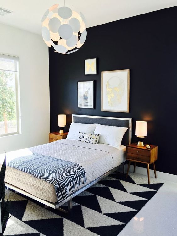 a bold and dramatic mid-century modern bedroom with a blakc statement wall, a geometric rug, a black bed and rich-stained nightstands
