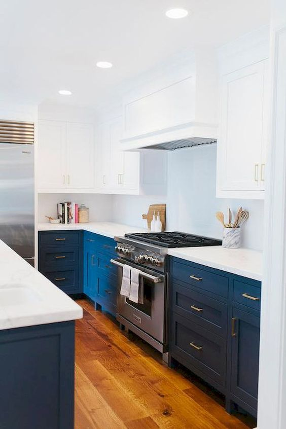 a bold blue and white mid-century modern kitchen with white countertops and a metal cooker