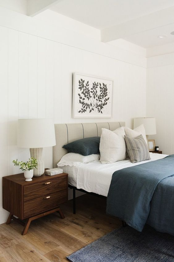 a bold mid-century modern bedroom with a grey leather bed, dark stained nightstands, navy rugs and bedding