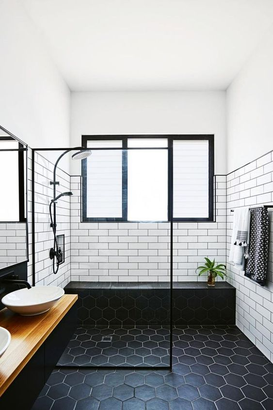 a bold monochromatic bathroom with white subway tiles and black hex ones, a floating vanity and bowl sinks plus black fixtures
