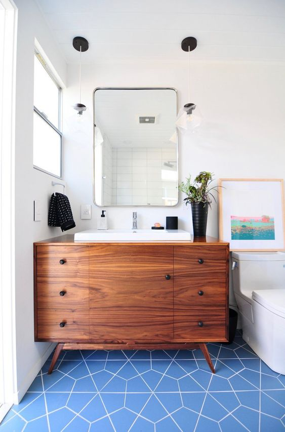 a bright mid-century modern bathroom with blue geo tiles on the floor, a rich stained vanity and touches of black for accenting