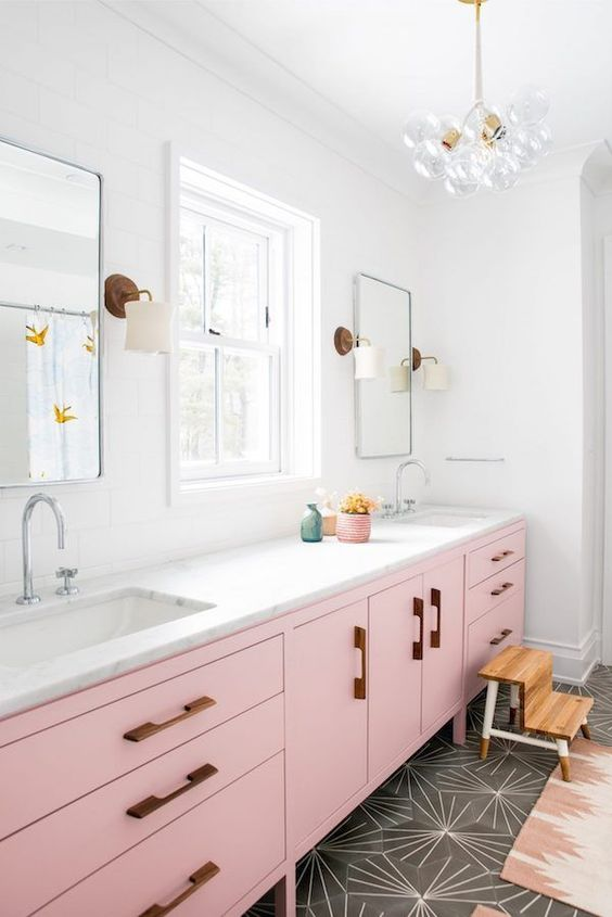 a bright mid-century modern bathroom with grey geometric tiles, a light pink vanity, touches of stained wood and gold