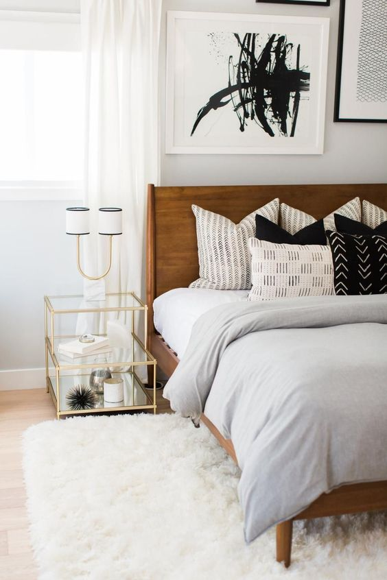 a bright mid-century modern bedroom with a rich stained bed, a white fluffy rug, a gilded frame nightstand and an abstract artwork