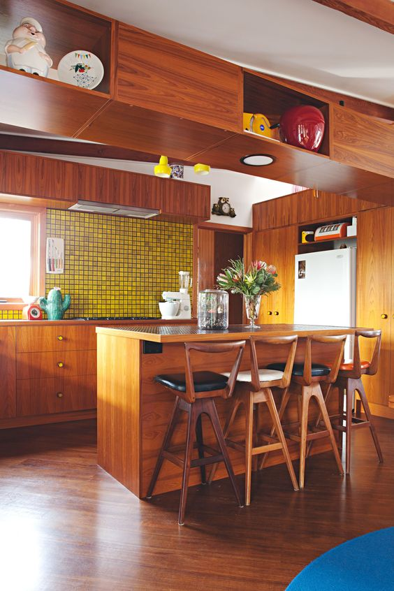 a bright mid-century modern kitchen with rich-stained cabinets, a yellow tile backsplash and tall wooden stools with backs