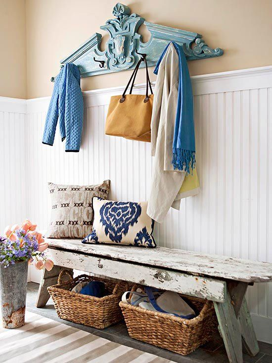 a bright shabby chic entryway with white shiplap, a wooden bench, baskets, pillows and a blue clothes hanger