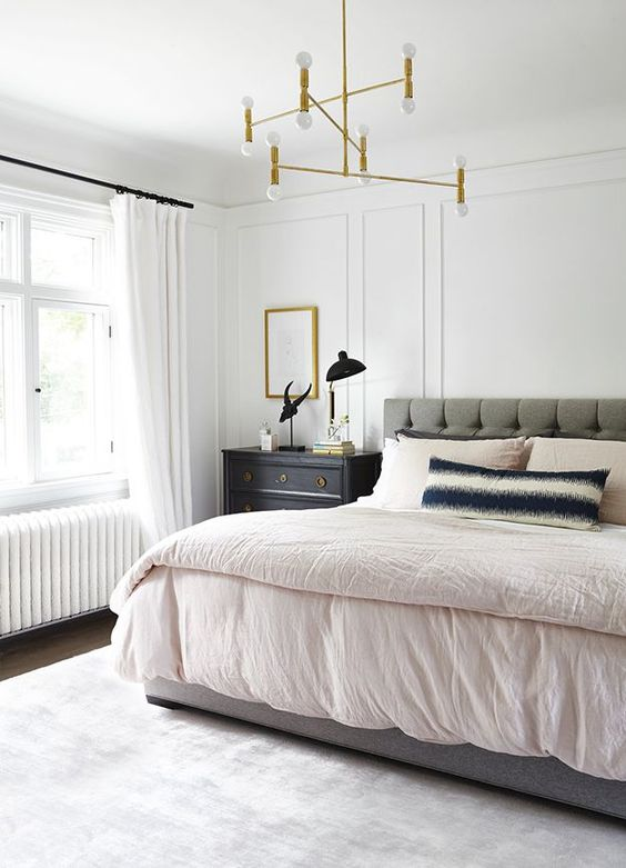 a calming mid-century modern bedroom with a grey upholstered bed, a gilded chandelier, dark stained nightstands and a neutral rug