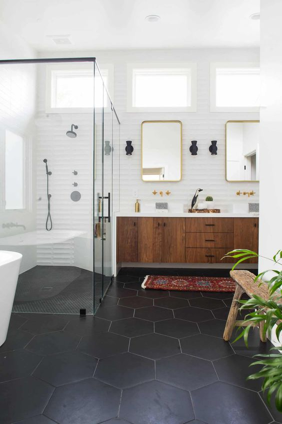 a chic mid-century modern bathroom with black hex tiles on the floor, a boho rug, a wooden floating vanity and touches of gold