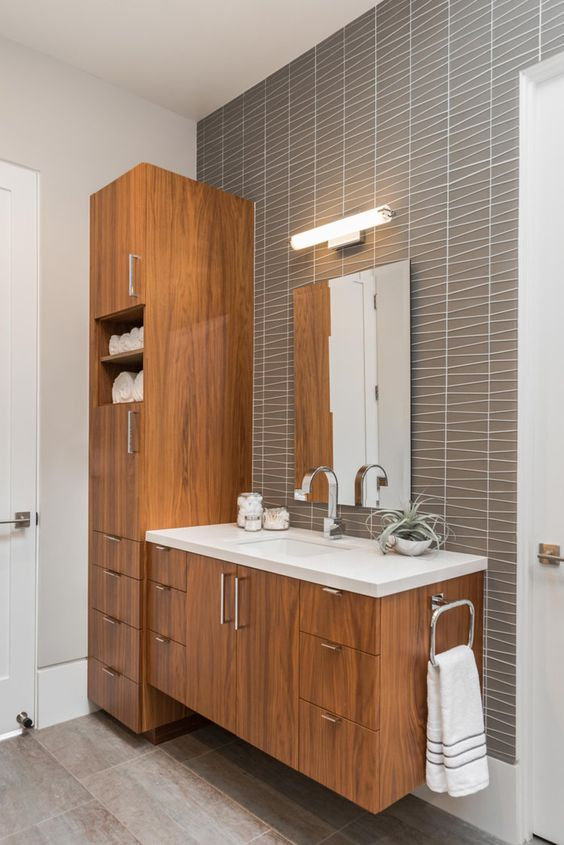 a chic mid-century modern bathroom with catchy grey tiles, stained wooden furniture, a mirror with a lamp over it