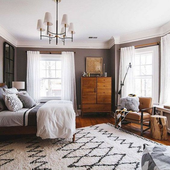 a chic mid century modern bedroom with a rich stained wooden dresser, a leather chair, a printed rug and a chic chandelier