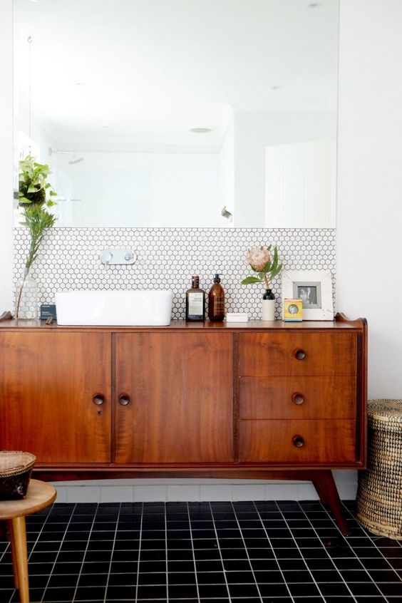 a chic mid-century modern space with white hex tiles and black usual ones, a rich stained vnaity and a statement mirror
