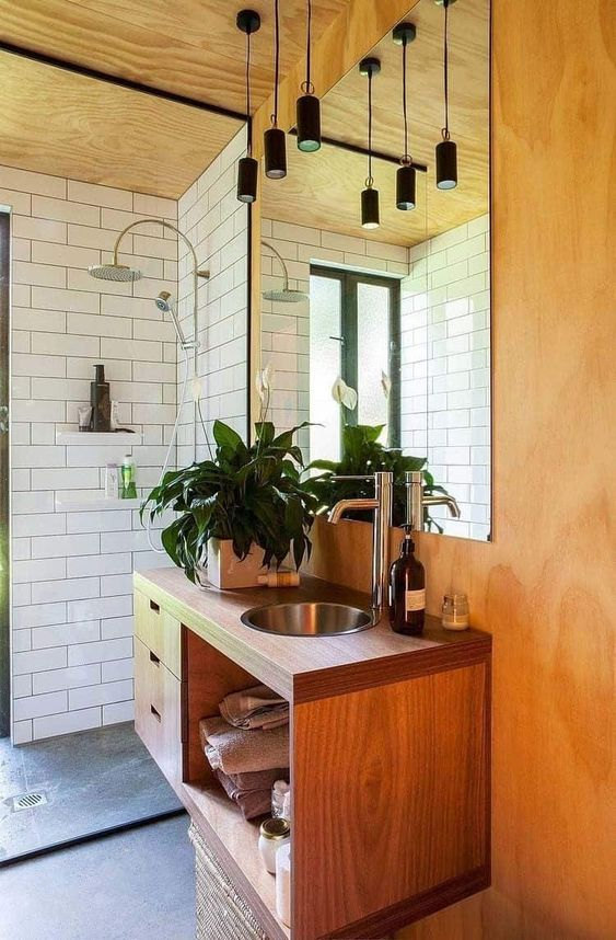 a chic mid-century modern space with white subway tiles, lots of plywood and wood, black pendant lamps over the sink