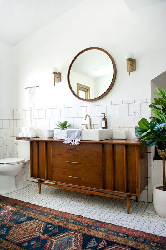 a classic mid-century modern bathroom with white square and penny tiles, a boho rug, a wooden vanity and touches of brass