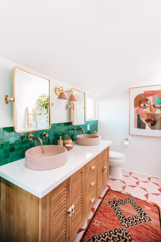 a colorful mid-century modern bathroom with green tiles for a backsplash, mosaic ones on the floor, pink sinks and lamps and a catchy wall art