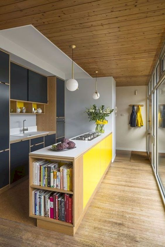 a colorful mid-century modern kitchen with navy cabinets, a yellow kitchen island and sphere lamps