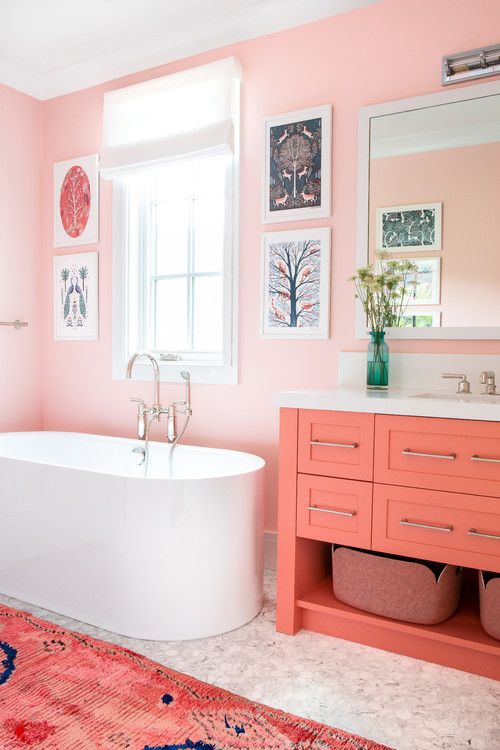 a colorful mid-century modern space with light pink walls, marble tiles, a coral vanity and a bright pink rug and a gallery wall