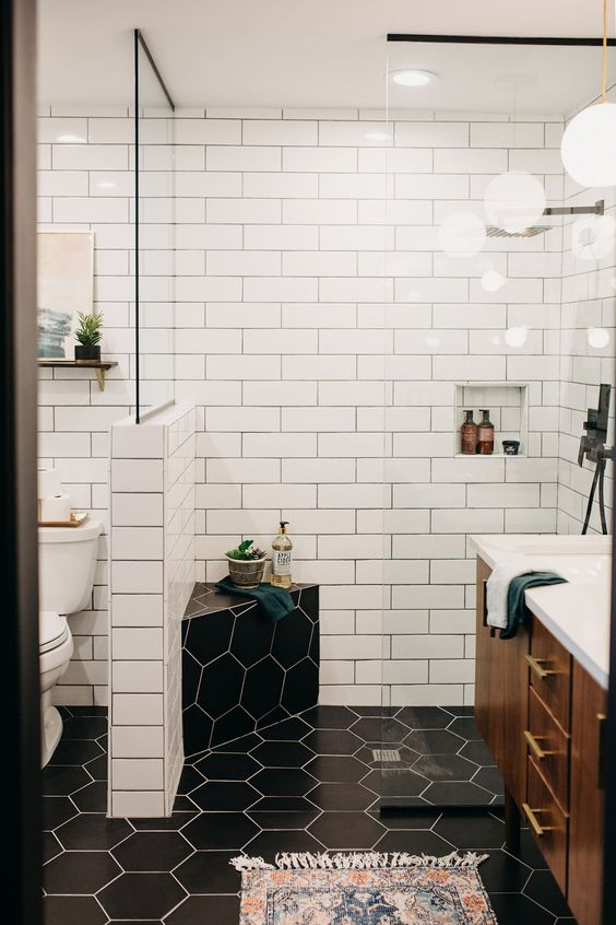 a contrasting mid-century modern bathroom with white subway and black hex tiles, a rich stained vanity and touches of gold