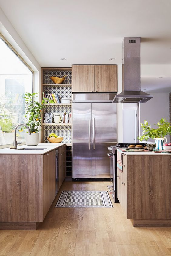 a cozy mid-century modern kitchen with mosaic tiles, wooden cabinets and metal appliances