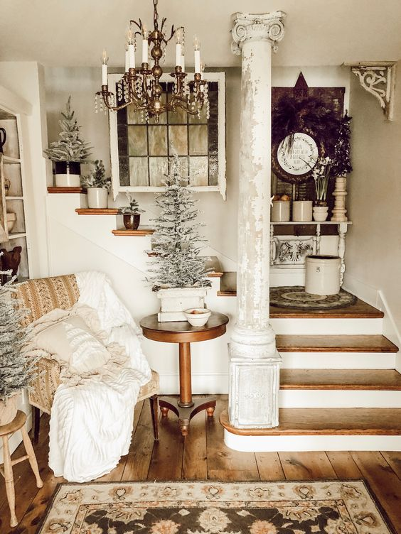 a cozy shabby chic entry with an upholstered chair, a wooden table, snowy trees in pots and a rug