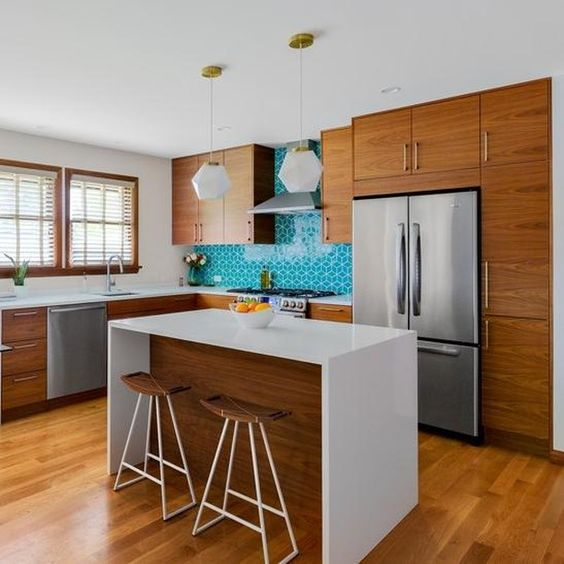 a cozy yet small mid-century modern kitchen with rich-stained cabinets, a turquoise tile backsplash, pendant lamps and a kitchen island