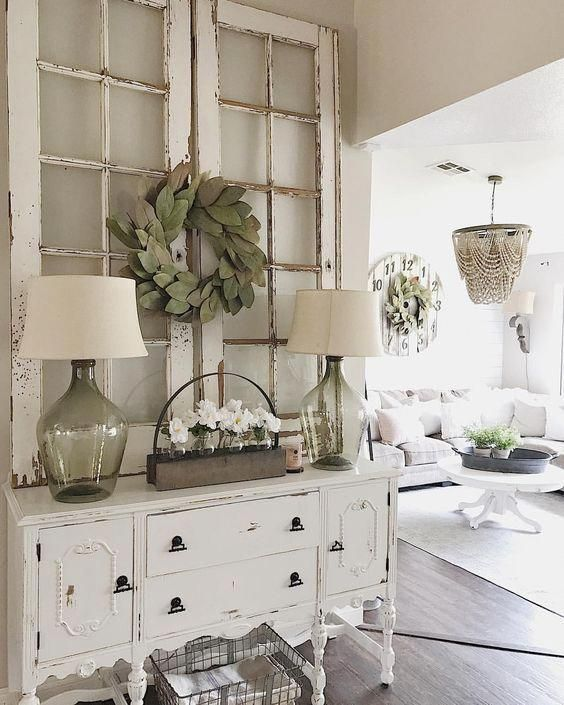 a cute shabby chic entryway with a chic sideboard, a wire basket, lamps, frames with a greenery wreath