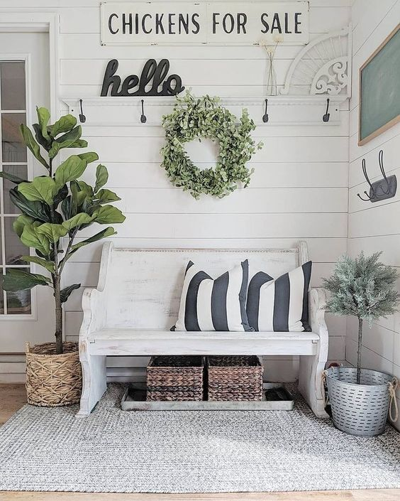 a farmhouse meets shabby chic entryway with signs, a white bench, baskets and potted greenery and trees