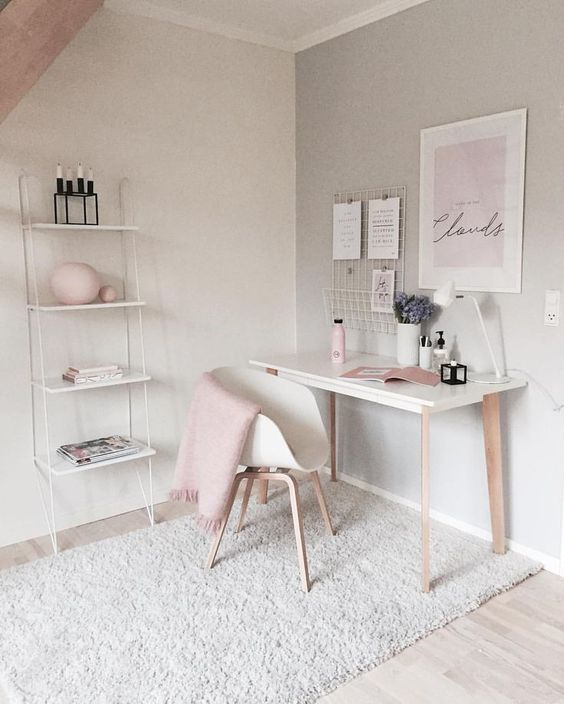 a feminine home office with touches of blush and wall-mounted shelving unit that is delicate and airy