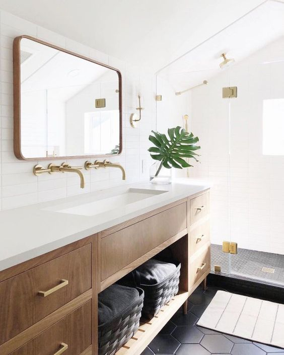 a gorgeous light-filled mid-century modern bathroom with windows, black hex tiles and skinny white ones, a wooden vanity and touches of gold