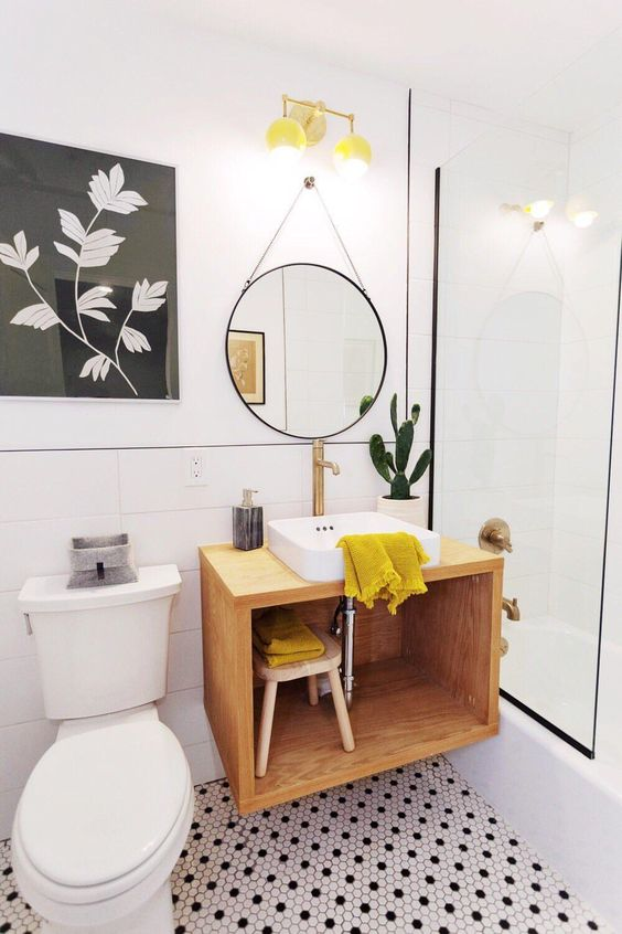 a gorgeous monochromatic bathroom with penny tiles and a floating vanity plus touches of mustard to make it bright