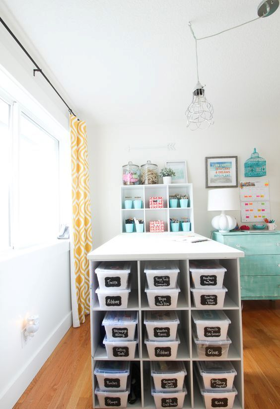 a large crafting table with shelves and boxes inside plus chalkboard labels