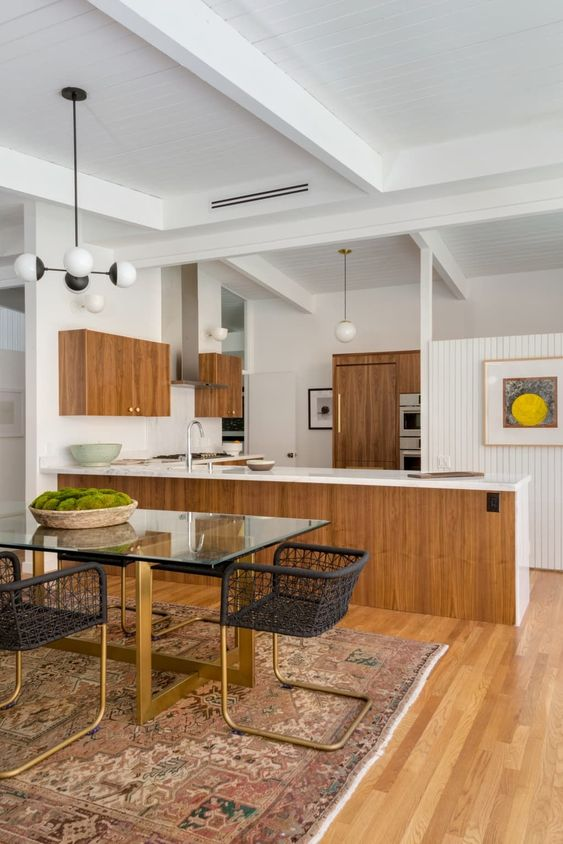 a large mid-century modern kitchen with wooden cabinets, white backsplashes and countertops