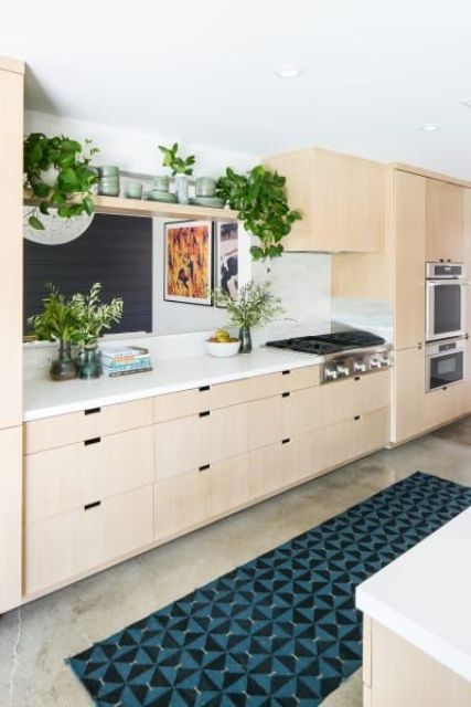 a light-colored mid-century modern kitchen of plywood, a mosaic rug and much greenery