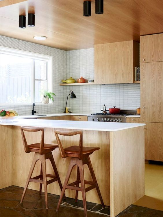 a light-colored mid-century modern kitchen with white countertops and tiled walls plus wooden stools
