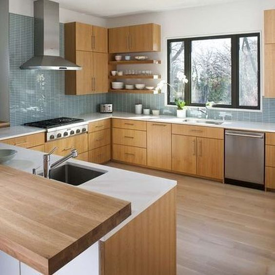 a light-colored wooden kitchen with white countertops, a blue tile backsplash and metal appliances