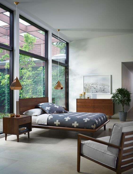 a light filled mid century modern bedroom with a glazed wall, rich stained wooden furniture, pendant lamps and a potted plant