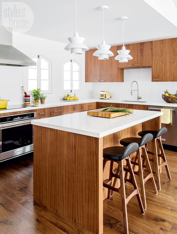 a light-filled mid-century modern kitchen with rich-stained cabinets, white countertops, white sculptural pendant lamps