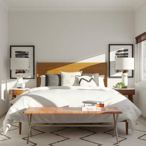 a mid-century minimal bedroom with monochromatic artworks, a leather bed, curved wooden nightstands, a matching bench