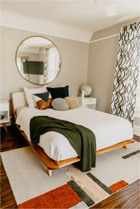 a mid-century modern bedroom with a geometric rug, a wooden bed, a round mirror, printed curtains and a variety of pillows