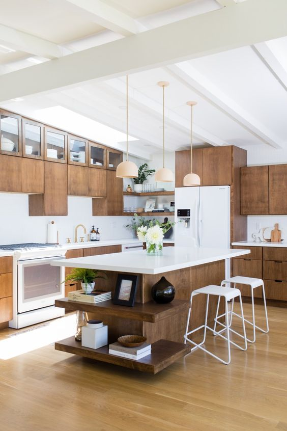 a mid-century modern kitchen with wooden cabinets, white countertops, pendant lamps and white stools