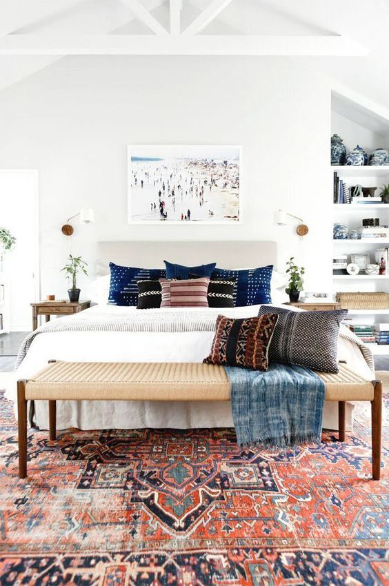 a mid-century modern meets boho bedroom with a boho rug, a woven bench, a built-in shelving unit and an artwork