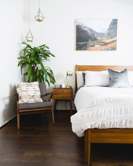 a mid-century modern meets boho bedroom with warm-colored wooden furniture, an artwork, pendant lamps and a potted plant